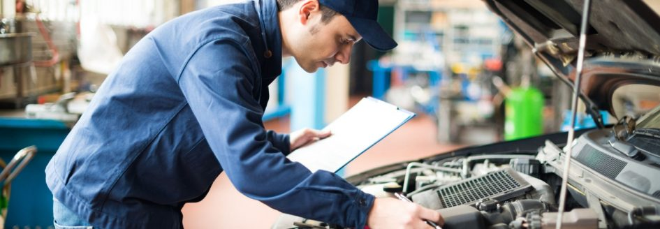 Car maintenance technician checking clipboard under the hood of car